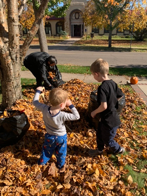 Dad and boys bagging leaves